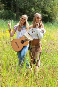21736110 - two retro blonde 70s hippie girls with sunglasses making music with acoustic guitar and tambourine outdoor in nature.
